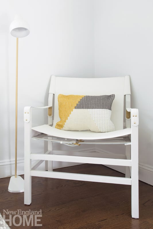 White chair in corner with yellow ad gray pilllow