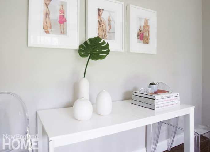 Contemporary white console with fashion photography