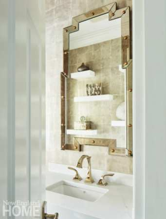 In the powder room, a wall-mounted sink allows easy access, and floating shelves in a niche on the wall provide a decorative pop.