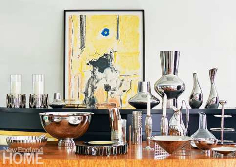 A large collection of Georg Jensen accessories stands in front of a Madame de Pompadour signed lithograph by Helen Frankenthaler.