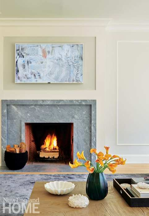 A textured collage by artist Joelle Somero hangs above the living room's fireplace.