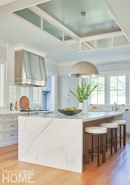 """The recess above the kitchen island is outfitted with silver Phillip Jeffries wallpaper on the ceiling and mirrors around the sides. """"It feels like it's open to the sky,"""" Butscher says. Again, the classic and contemporary blend in the Shaker cabinetry and the streamlined waterfall-edge island."""