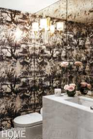In the powder room, a mirrored wall behind a marble Adige Design vanity reflects Jean Paul Gaultier wallpaper and a Circa Lighting sconce.