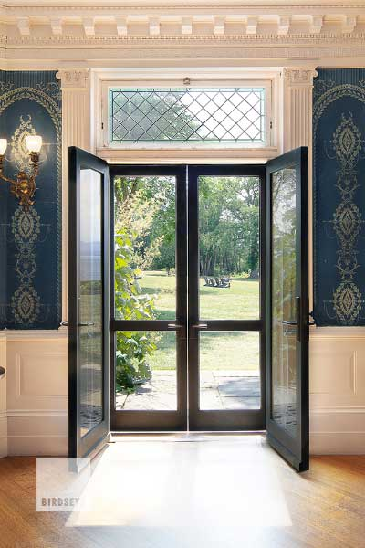 This set of paired doors was designed and built as a reproduction for a registered National Historic Landmark. In addition to being historically accurate, the doors needed modern refinements, such as ADA compliance, weather protection from a harsh north western exposure, and durability for use in a commercial restaurant setting. Photo by Lindsay Selin.