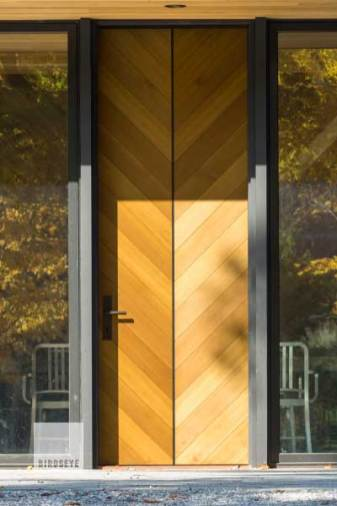 "This contemporary door, clad in western red cedar with steel accents, makes quite a statement, and also hints at the interior detailing of the home, where the split ""V"" cedar detail appears again on the chimney column above a large central fireplace. Extremely tight tolerances on all sides of this large door made for a challenging installation sequence and demanded a high degree of coordination from framing the rough opening through the applying the final trim. Photo by Jim Westphalen"
