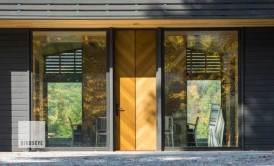 "This contemporary door, clad in western red cedar with steel accents, makes quite a statement, and also hints at the interior detailing of the home, where the split ""V"" cedar detail appears again on the chimney column above a large central fireplace. Extremely tight tolerances on all sides of this large door made for a challenging installation sequence and demanded a high degree of coordination from framing the rough opening through the applying the final trim. Photo by Jim Westphalen."
