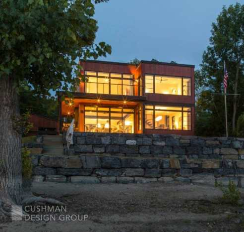 The site positioning and window-clad exterior connect this contemporary home to the rugged shore and lake beyond. Photo by Susan Teare.
