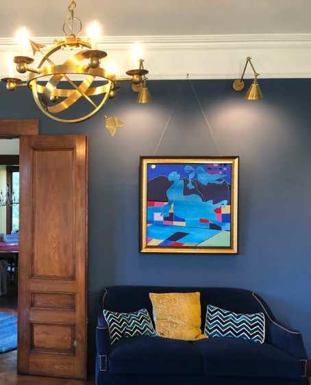 Visual Comfort's Armillary Sphere Chandelier and Double-Arm Library Light add glow to a living room painted in a deep navy paint.
