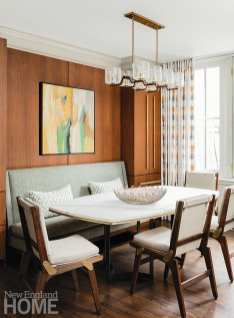 Dining area with a banquette and walnut paneling
