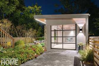 A driveway of gray pavers leads to the 350-square-foot garage where the owners can tandem park two cars. It also boasts an electric vehicle charging station. A spruce fence with a horizontal shadowbox design will weather to gray and fade into the background.