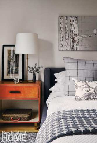 Bedroom with plaid pillows and wood night stand.