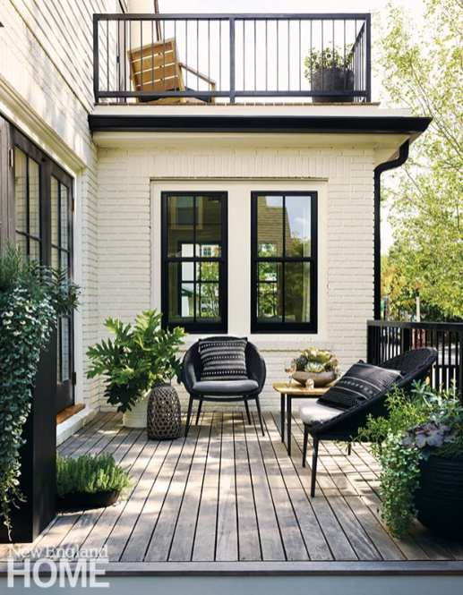 The backyard dining patio has a bluestone floor, a black-painted cedar fence, and simple plantings of trees and flowers that attract birds.