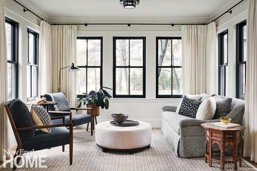 Neutral sunroom with round ottoman.