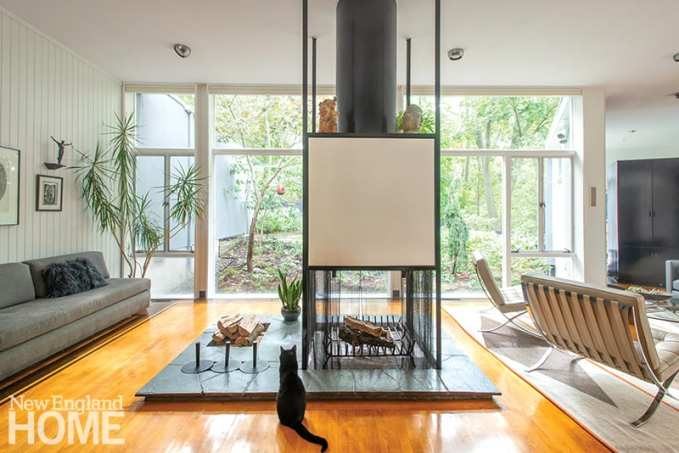 Family cat Curious George lives outdoors vicariously thanks to the glass wall in the home's open-plan living/dining room. The cleverly designed fireplace features sunken cavities to hold firewood and hide andirons. A gray built-in L-shaped sofa came with the house.