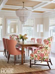 Dining room with white chandelier and pink chairs