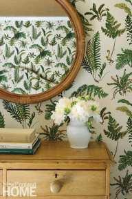 Dresser in a bedroom with fern wallpaper.