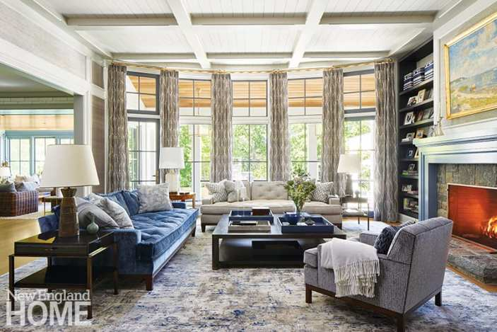 Living room with blue velvet sofa and patterned window treatments