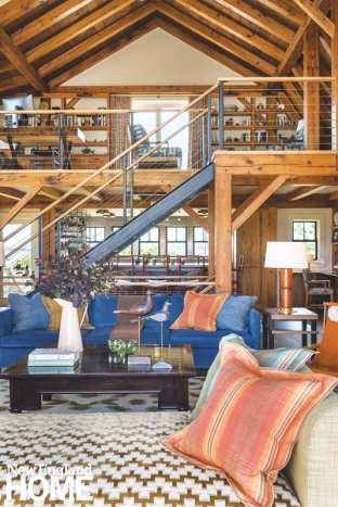 Converted barn living room with a blue couch and assorted textiles.