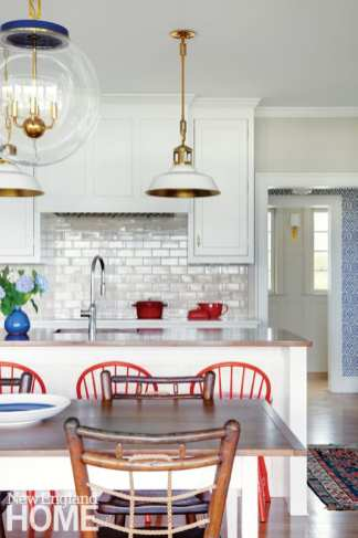White kitchen with white and brass light fixtures.