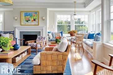 Coastal living room with rattan furniture and a blue rug.