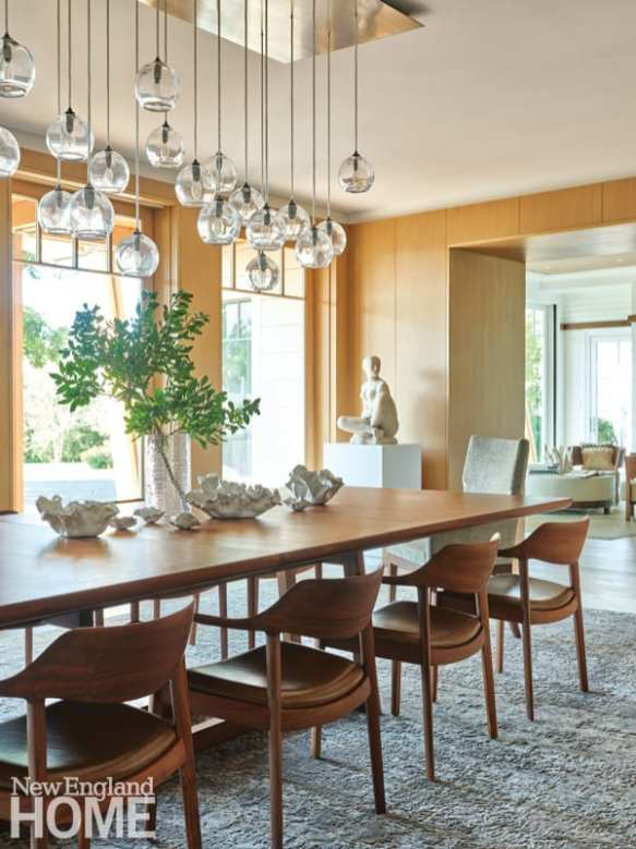 The dining room is paneled with cerused, rift-sawn white oak. A John Pomp light fixture hangs above a table, designed by de Santaren and crafted by Masterpiece Woodworks of Avon, Massachusetts.