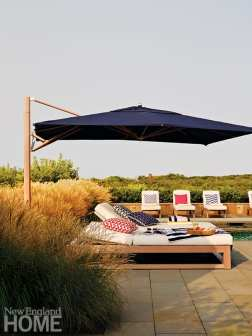 Double chaise lounge with large navy blue umbrella