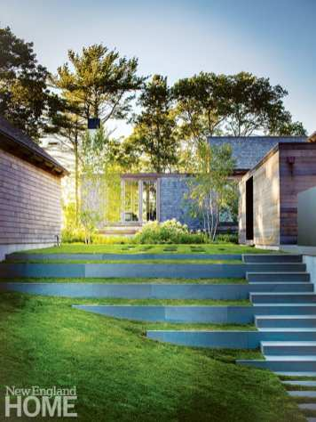"""Behind the garage, a white garden blossoms between the path and linear concrete retaining walls that modulate the slope toward the pool. """"The dramatic hillside setting, the woodland, and the marsh beyond all spoke to us as we designed the landscape,"""" says landscape architect Kris Horiuchi."""