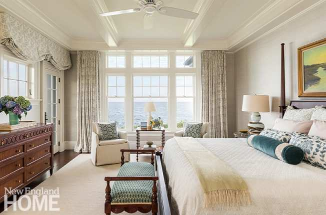 The homeowners wake up to water views in their east-facing suite; the ceiling's millwork hides the motors that open and close the drapes and blackout shades.