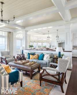 """For the family room, Watson revved up the palette, incorporating hues suggestive of a summer sunset in toss pillows and the area rug that sits atop a woven rug. """"In a large open space like this, layering rugs is a way to, literally, add a layer of interest,"""" the designer says."""