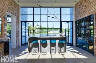 Opposite the atrium's front door, a bar overlooks Five Mile River; the turquoise hair-on-hide barstools are from Holly Hunt.