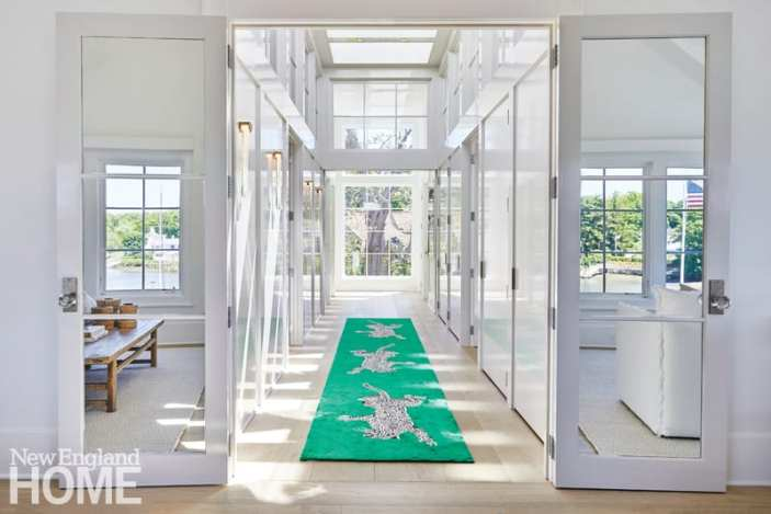 Lacquered walls in the suite's hallway amplify the natural light, while the grass-green rug by Diane Von Furstenberg for The Rug Company leads the eye to a view of the property's catalpa tree.