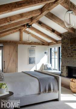 More beams, a fireplace built of ledge, and window benches remove any pretension from the primary bedroom suite.