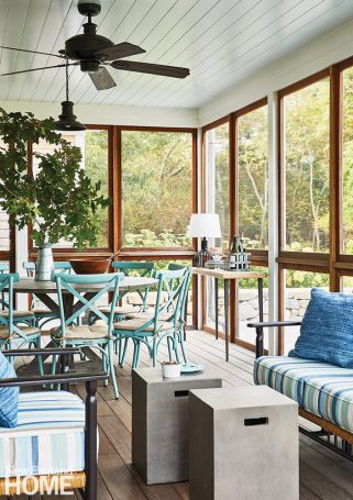 Screened porch with a dining table with turquoise chairs.