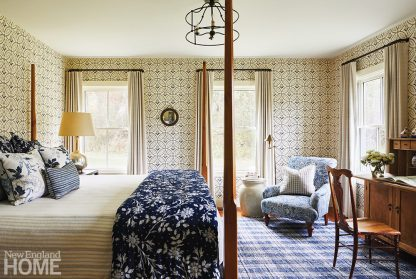 Bedroom with historical blue and white patterned wallpaper.