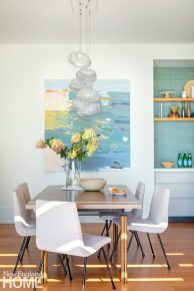 Contemporary dining area with light wood table and white chairs.