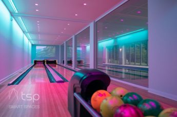 Home automation takes a fun spin in this home bowling alley and indoor pool, highlighted by Ketra lighting and Lutron shades.