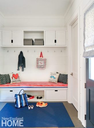 white mudroom with red upholstered bench and blue rug.