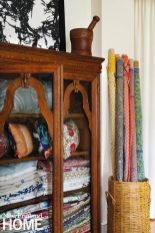 Antique cabinet full of pillows and linens