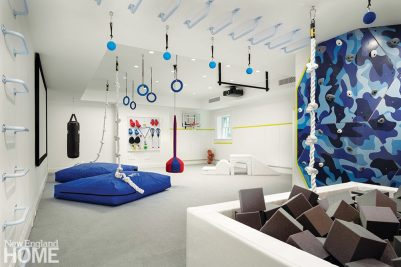 Children's playroom designed with trapeze, mats, and foam block pit.