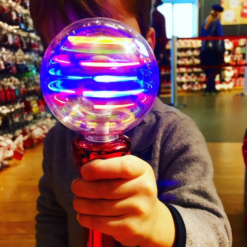 child holding a spinning light toy