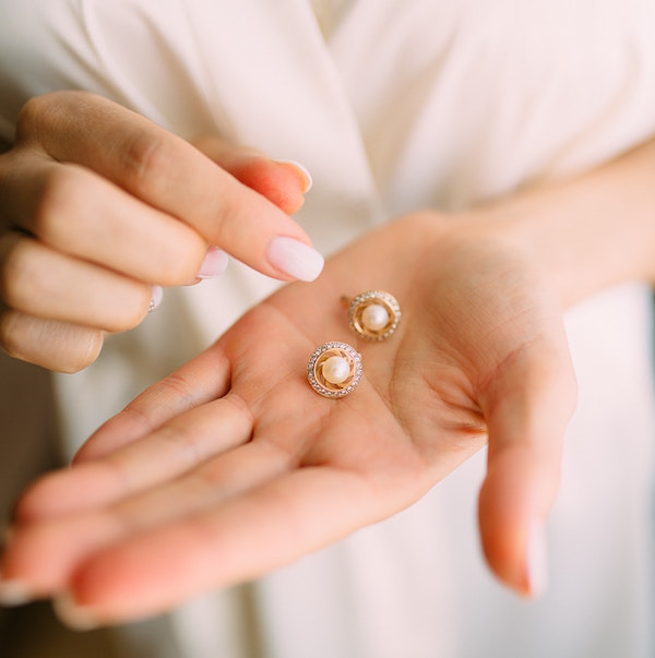 a woman holds a pair of expensive earrings