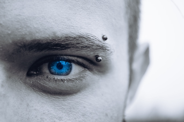 Man with eyebrow piercing and curved barbell jewelry