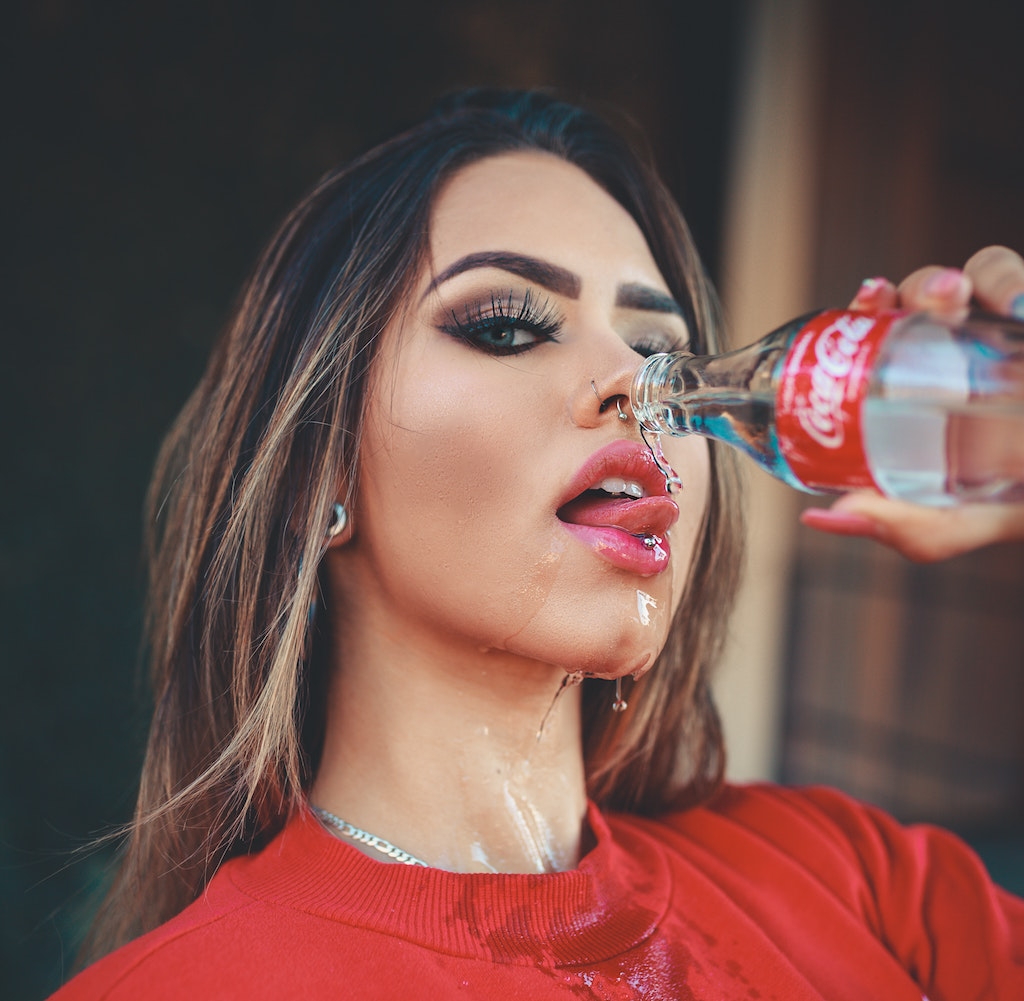 woman with tongue piercing drinking water