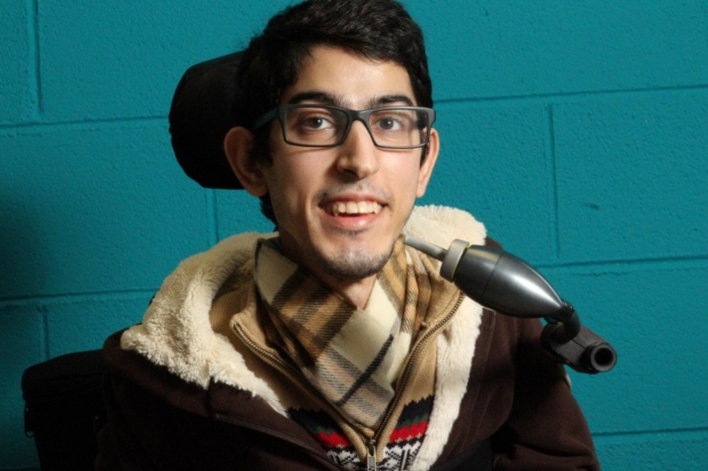 a young man in a wheelchair happy to have access to his mobile device through the LipSync.