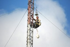 The technician was hoisted up the tower in a chair rather than having to climb.