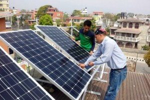 Representatives of Gham Power Pvt. Ltd. install solar panels at Biruwa Ventures in Kathmandu. Gham Power has already installed solar systems in more than 300 households and 50 institutions. The company provides financing to offset initial high costs.