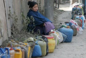 A girl waits with empty containers to buy kerosene, the main cooking fuel, in the Nepali capital of Kathmandu, Feb. 26, 2008. REUTERS/Gopal Chitrakar