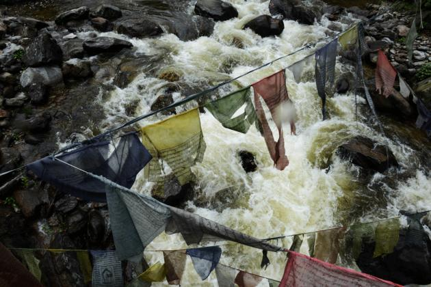 River water rushes past prayer flags on its way to the intake water tunnel at the Chukha hydropower plant in mountains in south eastern Bhutan.