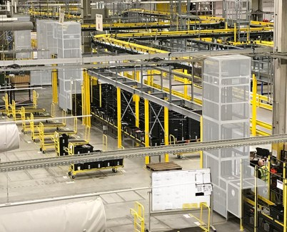 Multiple Boxlifters move Boxes and Totes around an E-Commerce Distribution Centre linking a vast networks of lower and overhead conveyors