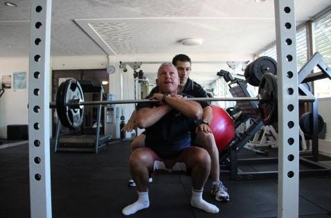 A Personal Trainer assisting a client.